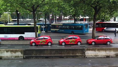 deelauto van Greenwheels met bussen op achtergrond