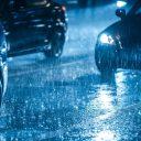 Auto rijdt 's nachts door de regen BEELD iStock