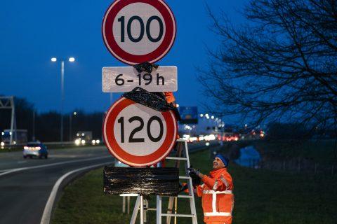 GROENEKAN - Een medewerker van Rijkswaterstaat onthult een 100 kilometer-bord. De verlaging van de maximumsnelheid op snelwegen wordt de komende tijd ingevoerd. ANP JEROEN JUMELET