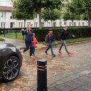 Schoolgaande kinderen voor auto in woonwijk