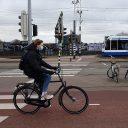 Fietsers met mondkapje voor tram GVB