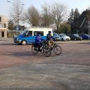 Senioren met helm op, op de fiets op kruispunt